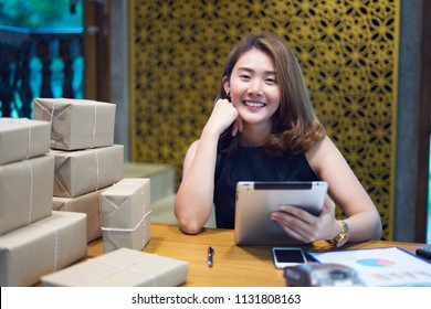 Happy asian women working tablet from home on desk with postal parcel, Female buyer touch screen of tablet buy presents, among gift boxes and packages. online shopping. Selling online ideas concept.