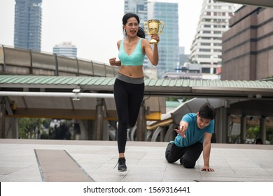 Happy Asian young beatiful woman winner raise gold trophy to celebrate running victory while male loser runner fall on footpath in modern city. Sport and Competition concept
