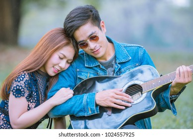Happy Asian young couples romance sitting in the park and playing the guitar to his beloved girl.