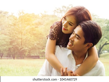 Happy Asian young couples romance sitting enjoying spending time together in love outdoor, Two lovers are hugging each othe