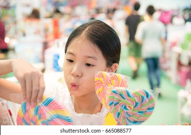 Happy Asian young girl buying colorful of sweets or lollipop in the store with blurred people background. Surprised pretty child with candy, unhealthy eating concept.
