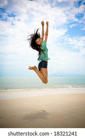 happy asian young girl jumping gracefully at the beach on sunny day