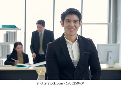 Happy asian young handsome smart successful business man smiling standing with team mates discussing in the background
