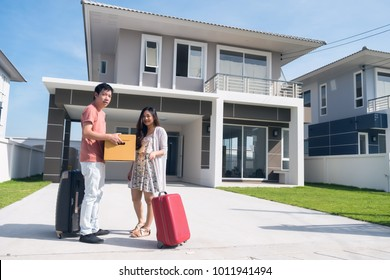 Happy Asian young husband and wife couple carrying box and luggage in front of new home. Portrait of couple moving to modern house. Family lifestyle to start. They bought first home