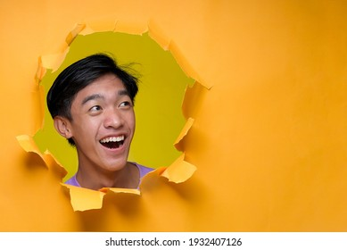 Happy Asian Young Man smiling look at a copy space, poses through torn yellow paper hole. Advertise Concept
