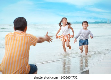 happy asian young single dad playing with his children boy and girl, they running on sandy beach during sunny day with laughing and smiling