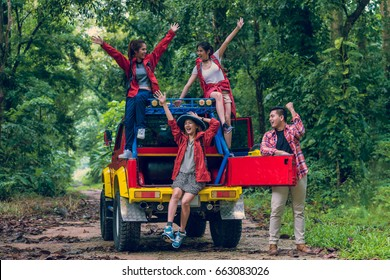 Happy asian young travellers with 4WD drive car off road in forest, young couple looking for directions on the map and another two are enjoying on 4WD drive car.