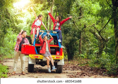 Happy asian young travellers with 4WD drive car off road in forest, young couple looking for directions on the map and another two are enjoying on 4WD drive car. Young mixed race Asian woman and man.