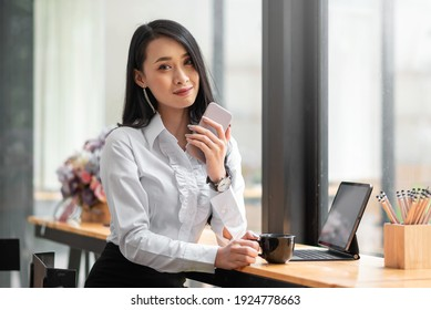 Happy Asian young woman drinking coffee at coffee shop holding phone. Looking at camera.