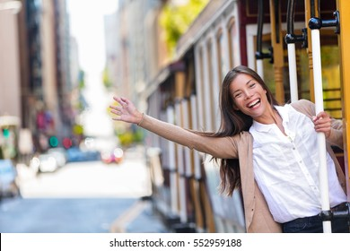 Happy Asian young woman excited having fun riding the popular tourist attraction tramway cable car system in San Francisco city, California during summer vacation. Tourism lifestyle.