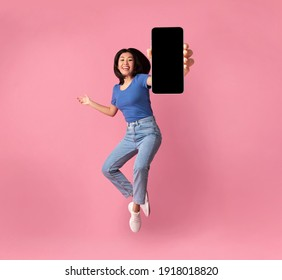 Happy asian young woman showing empty smartphone screen while jumping up over pink studio background, collage, full size photo. Excited lady recommending nice and useful mobile application