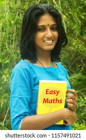 Happy Asian/Indian/Kerala girl/student/teacher holding a concept easy maths text book
