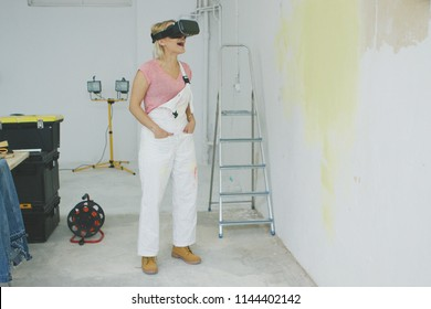 Happy astonished young blond woman with open mouth in white overalls experiencing virtual reality in goggles headset standing at half-painted wall and working desk with hands in pockets.
