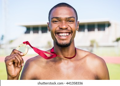 Happy athlete holding gold medal after victory in stadium