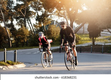 Happy athletic couple enjoying morning ride on racing bicycles, speeding on desert street. Young European man and woman cyclists wearing stylish sports clothing riding road bikes outdoors in city
