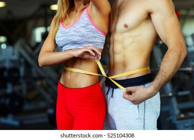 Happy athletic couple - man and woman with measuring tape in gym