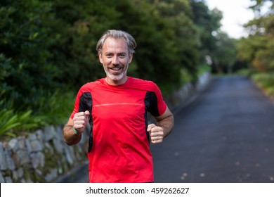 Happy athletic man jogging on the open road