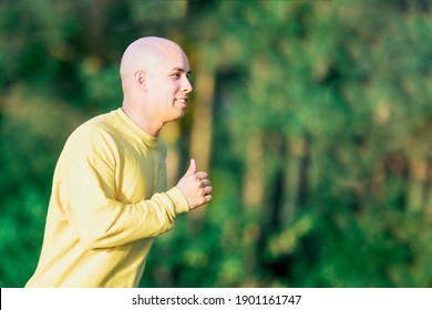 Happy athletic man jogging outdoors. Healthy lifestyle, fitness, sport and weight loss concept
