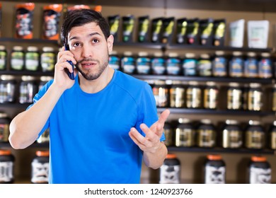Happy athletic man talking by phone  near shelves with sport nutrition in shop