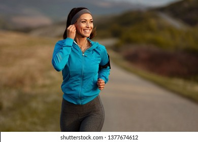 Happy athletic woman listening music on earphones while running in nature in the morning. Copy space.
