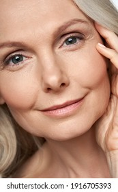 Happy attractive 50 years old middle aged mature woman touching healthy soft face skin looking at camera. Anti age dry skin care tightening treatment ads. Face close up view crop detail portrait