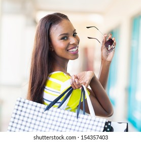 happy attractive african shopper in shopping mall