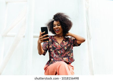 Happy attractive african woman, smiling cheerfully while looking at mobile phone screen. Dressed in colorful clothes. Sitting outdoors.
