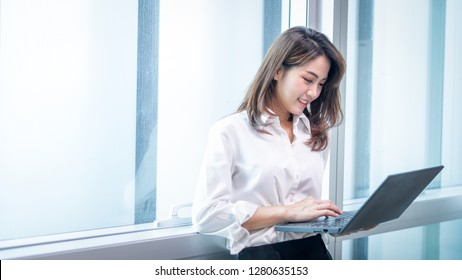 Happy attractive asian business woman  smiling working with laptop in modern office