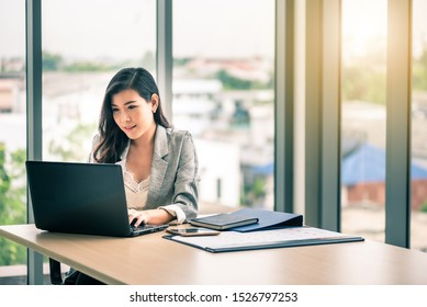 Happy attractive Asian business woman working with a laptop and financial document at office, successful action, Business concept.