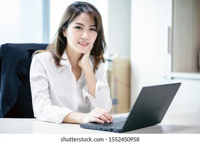 Happy attractive asian business woman smiling working with laptop