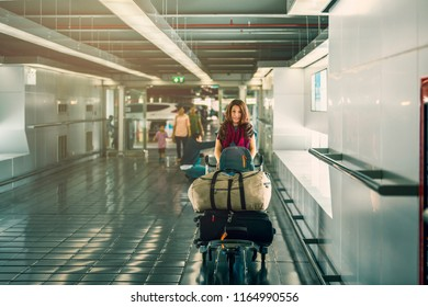 Happy attractive Asian woman passenger with luggage trolley walking in airport and cars parking on the background. Image with copy space