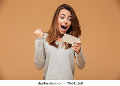 Happy attractive brunette girl joying win in video game on smartphone, isolated over beige background