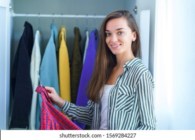 Happy attractive brunette woman choosing outfit from wardrobe closet with stylish clothes and home stuff