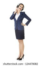 Happy attractive businesswoman listening the music through headphones