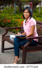 A happy and attractive college student in pink shirt sitting outside on bench smiling looking at camera and writing into her notepad.  20s female Asian Thai model of Chinese descent