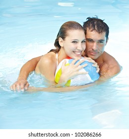 Happy attractive couple with beach ball in swimming pool