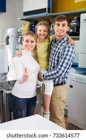 Happy attractive couple with girl in store with home electronics