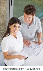 Happy attractive couple holding architectural drawing in their hands