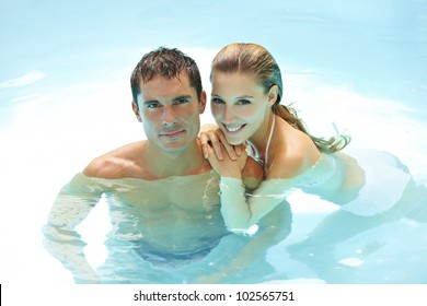 Happy attractive couple taking a bath in a swimming pool