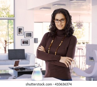 Happy attractive female casual caucasian interior designer at trendy luxury home, wearing glasses, standing arms crossed, looking at camera, smiling.