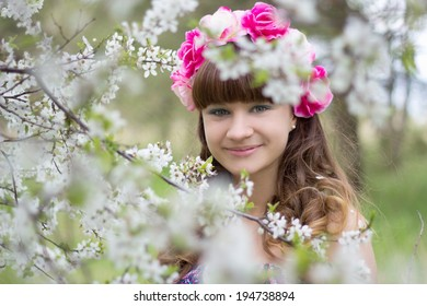 Happy attractive girl and blooming tree in garden