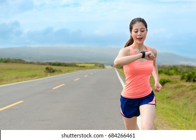 happy attractive girl runner using smartwatch system recording personal heart rate and confirm training route through GPS when she running on road workout.