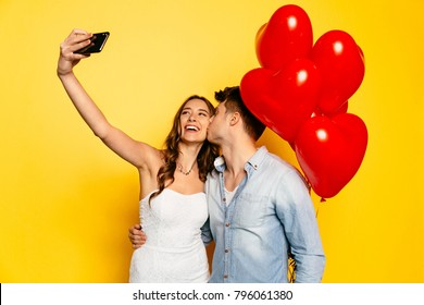 Happy attractive girl taking selfie on smartphone while her boyfriend kissing her in cheek, on yellow background with red balloons. Celebrating Valentine's day.