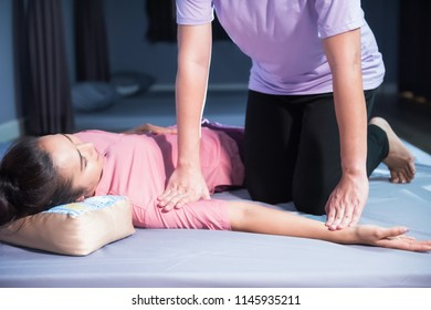 Happy attractive girl with traditional dress massaging hand and arm by professional massager. Portrait of Asian middle aged woman relax in spa. Body care treatment by Thai massage.