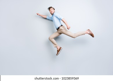 Happy, attractive, handsome, young man with bristle jumping in air showing superman pose looking at camera with beaming smile over grey background