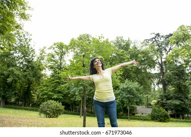 Happy attractive latin woman throwing her hands in the air outside relaxing in a green lush park or meadows