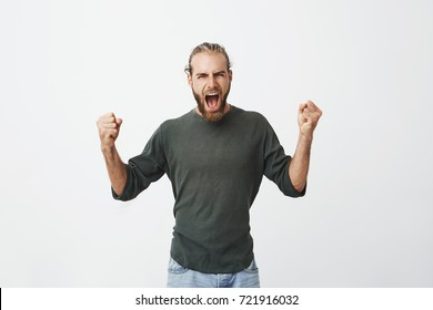 Happy attractive man with beard screaming loudly and expressive gesticulating with hands when his favourite football team finally won in match.
