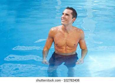 Happy attractive man standing in blue water in a swimming pool