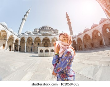 Happy attractive muslim woman in Istanbul, Turkey, posing in courtyard of Suleymaniye mosque, religion and travel concept.