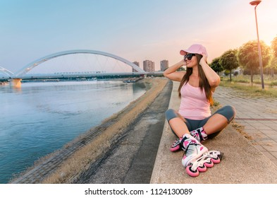 Happy attractive roller skater girl enjoying beautiful summer day